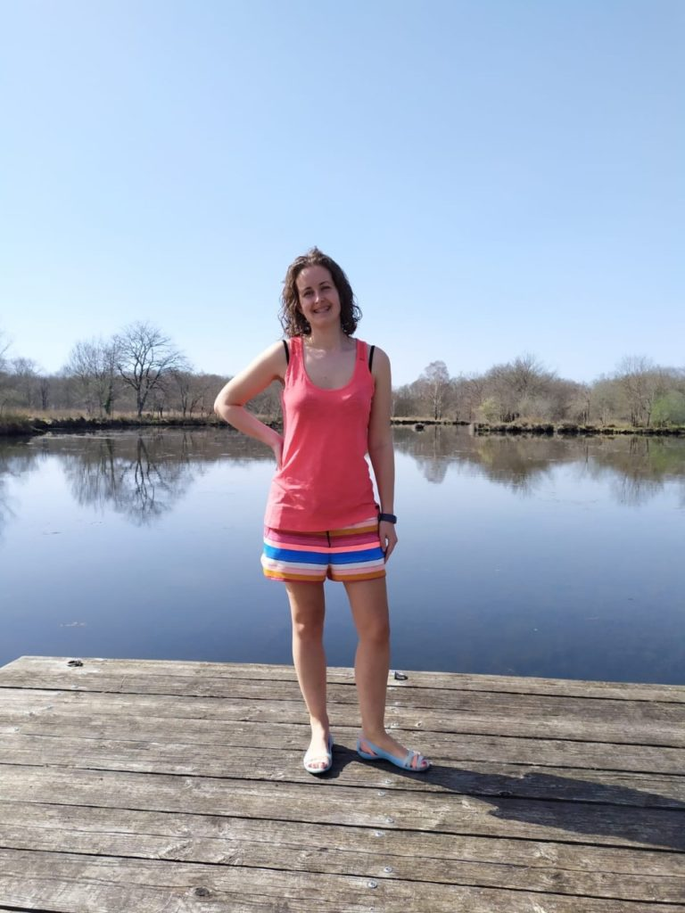 I am stood weraing a coral top and stripy shorts next to a lake