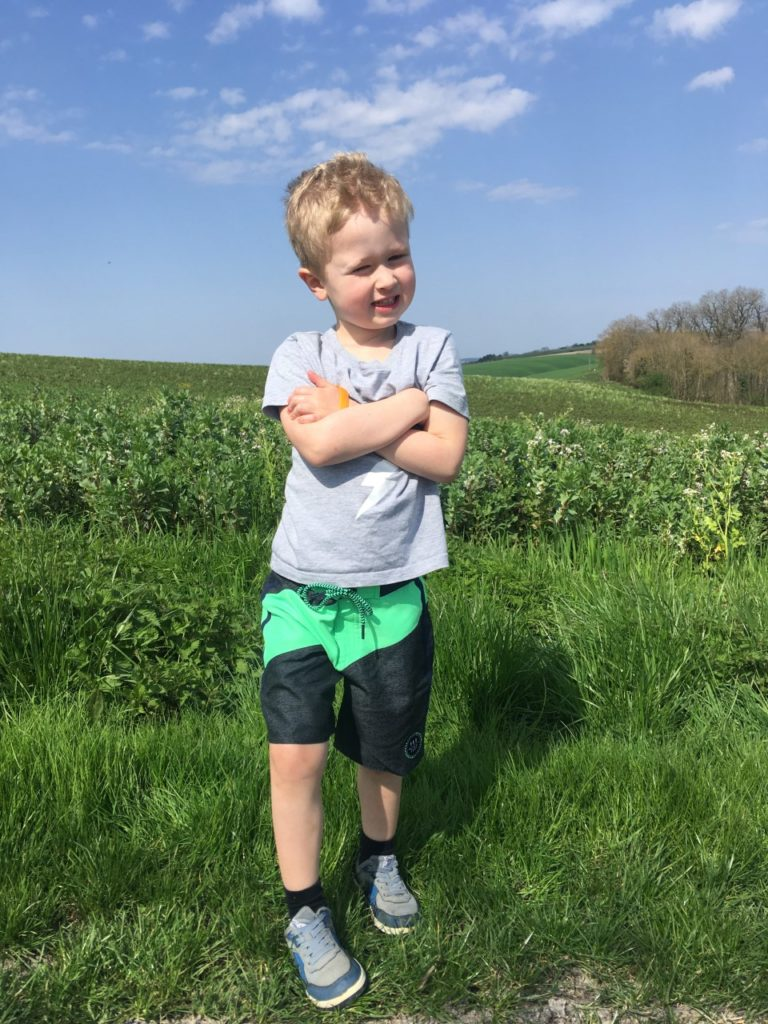 Lucas stood with fields behind him wearing a grey tshirt and his arms crossed. He has protest grey and green shorts on
