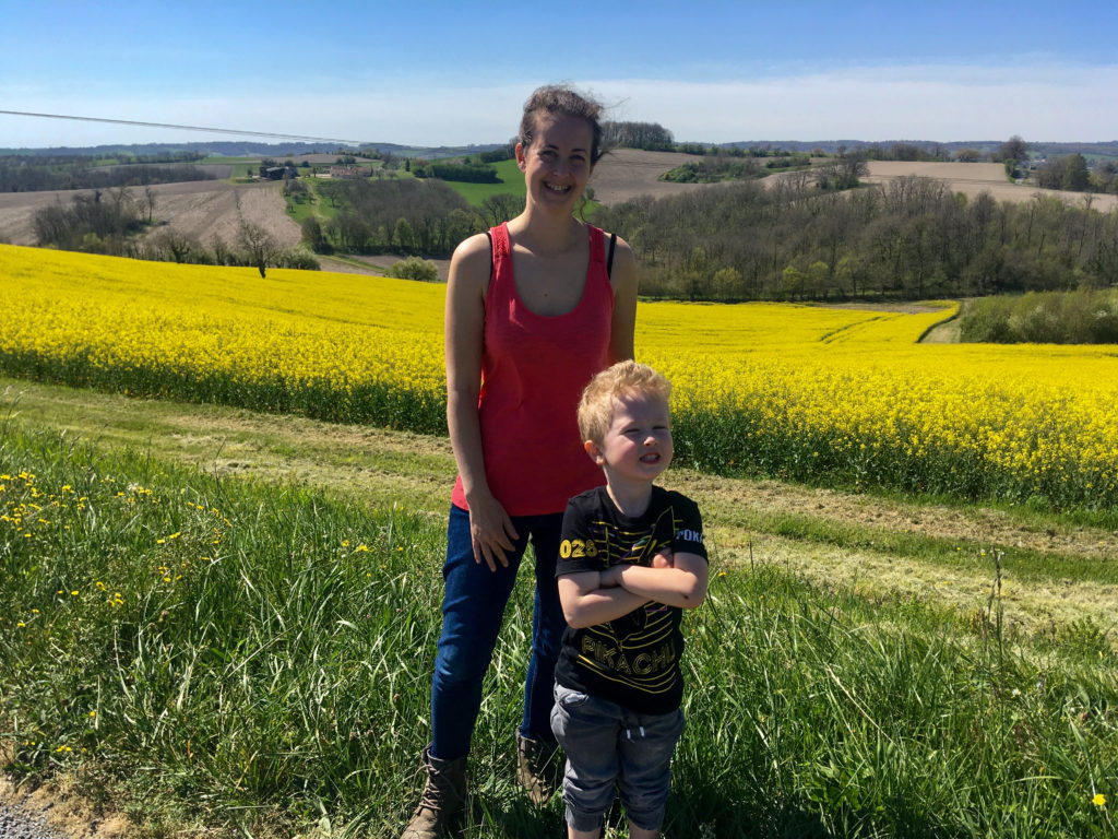 Lucas and I stood in front of a yellow rapeseed field on a sunny day