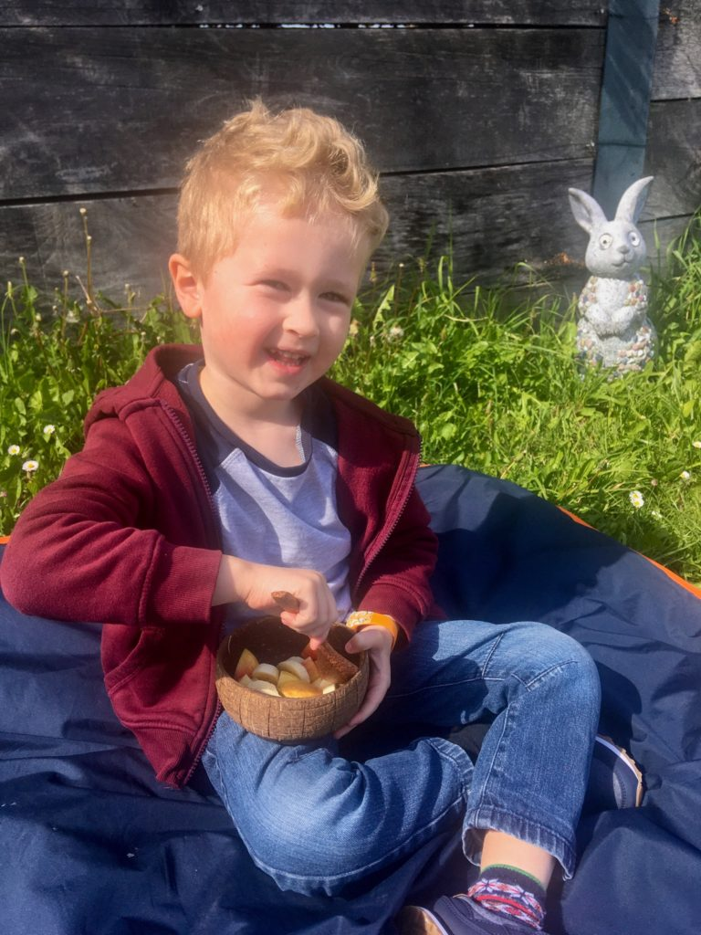 Lucas sat out on the grass on a picnic blanket eating fruit salad from a coconut bowl