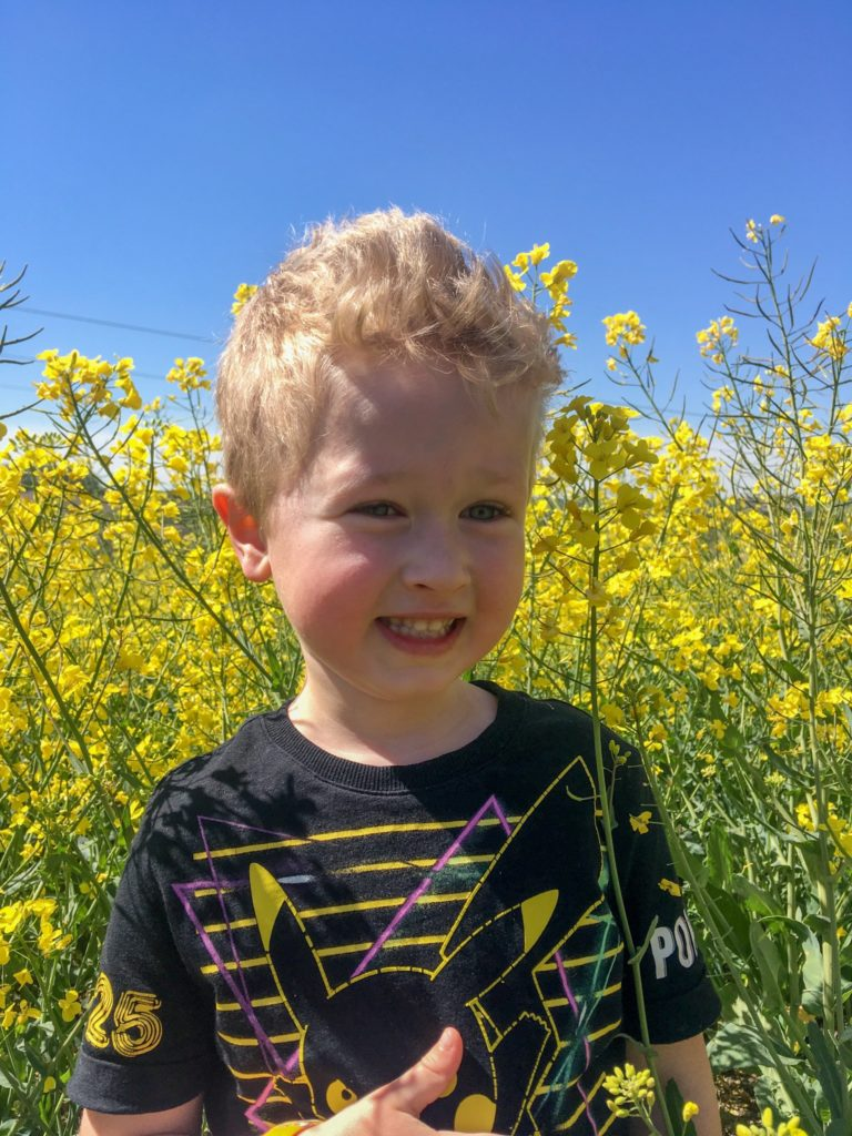 A close of of lucas smiling next to a yellow rapeseed field