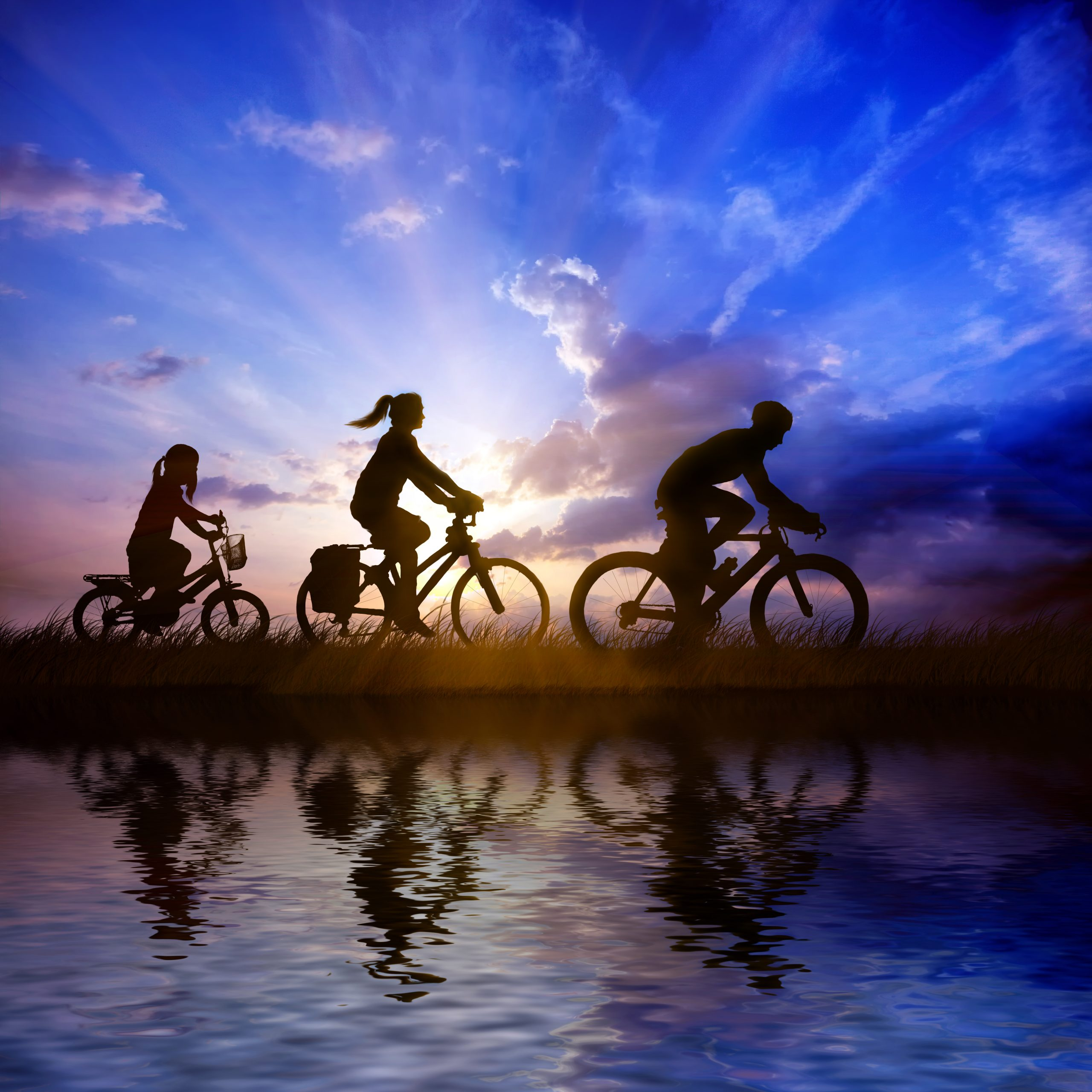 Going cycling with children. The photo shows two adults and a child cycling in the evening with a sunset behind
