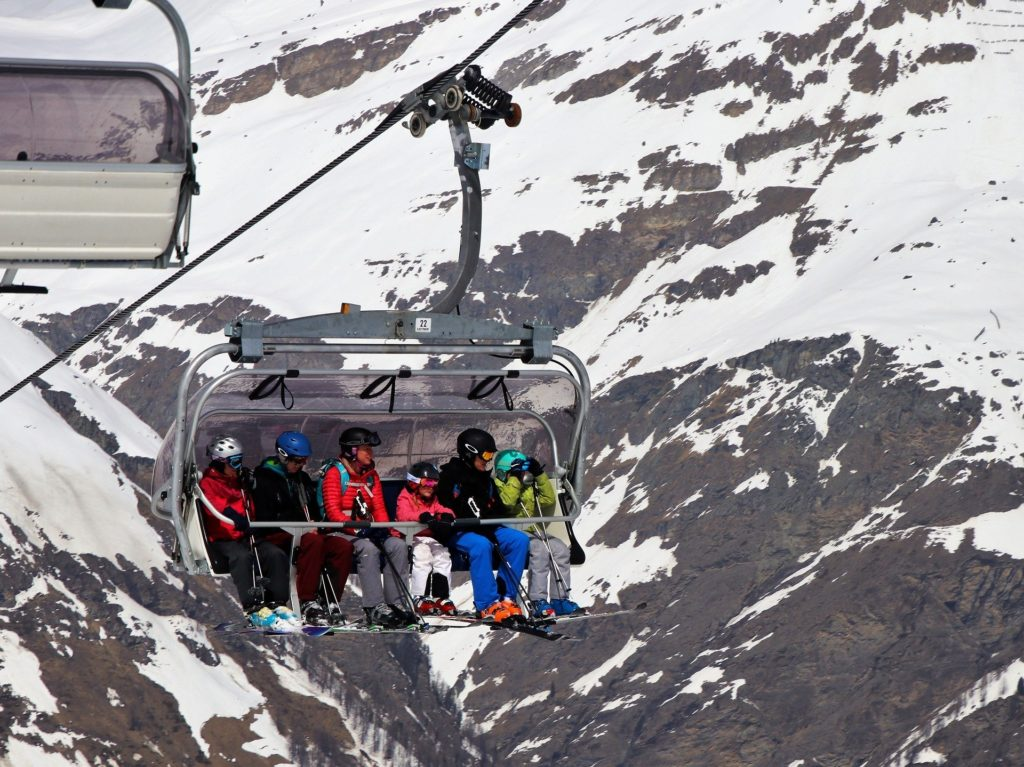 a cable car in the mountains showing a family of skiers sat down