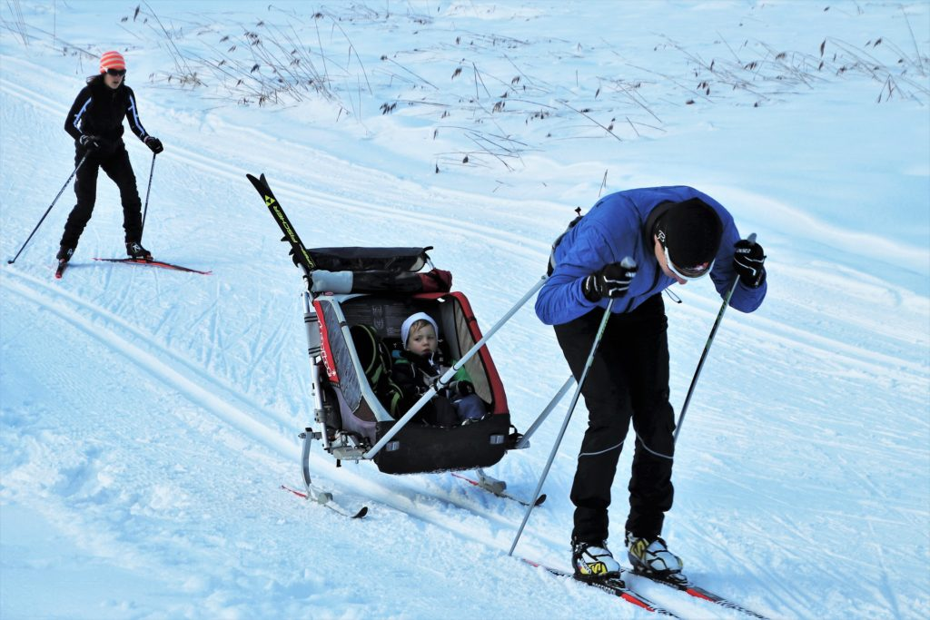 family ski holiday, you can see an adult man skiing, pulling along a toddler in a ski cart with an adult female skiing behind