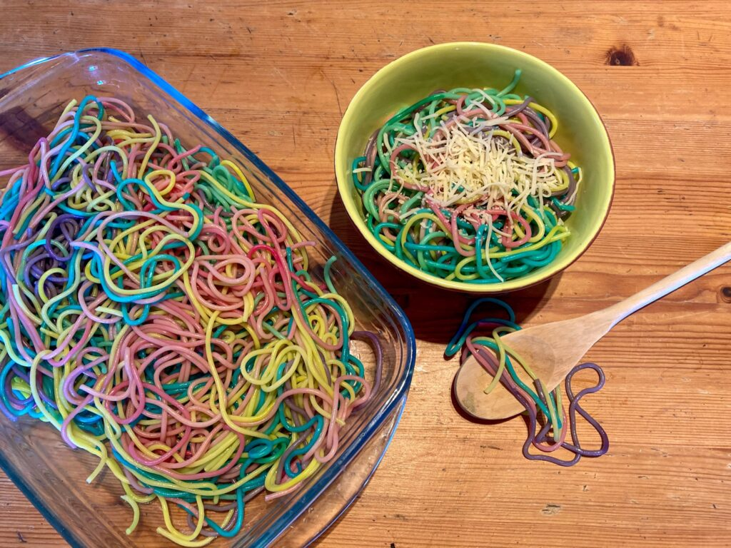 Rainbow spaghetti in an eating bowl next to a bowl full of spaghetti in a serving dish and wooden spoon