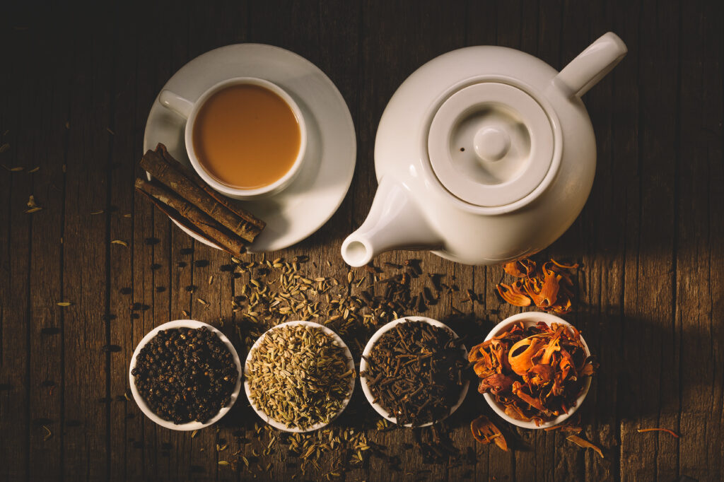 Various types of tea leaves in pots next to a white tea pot and cup of tea next to it
