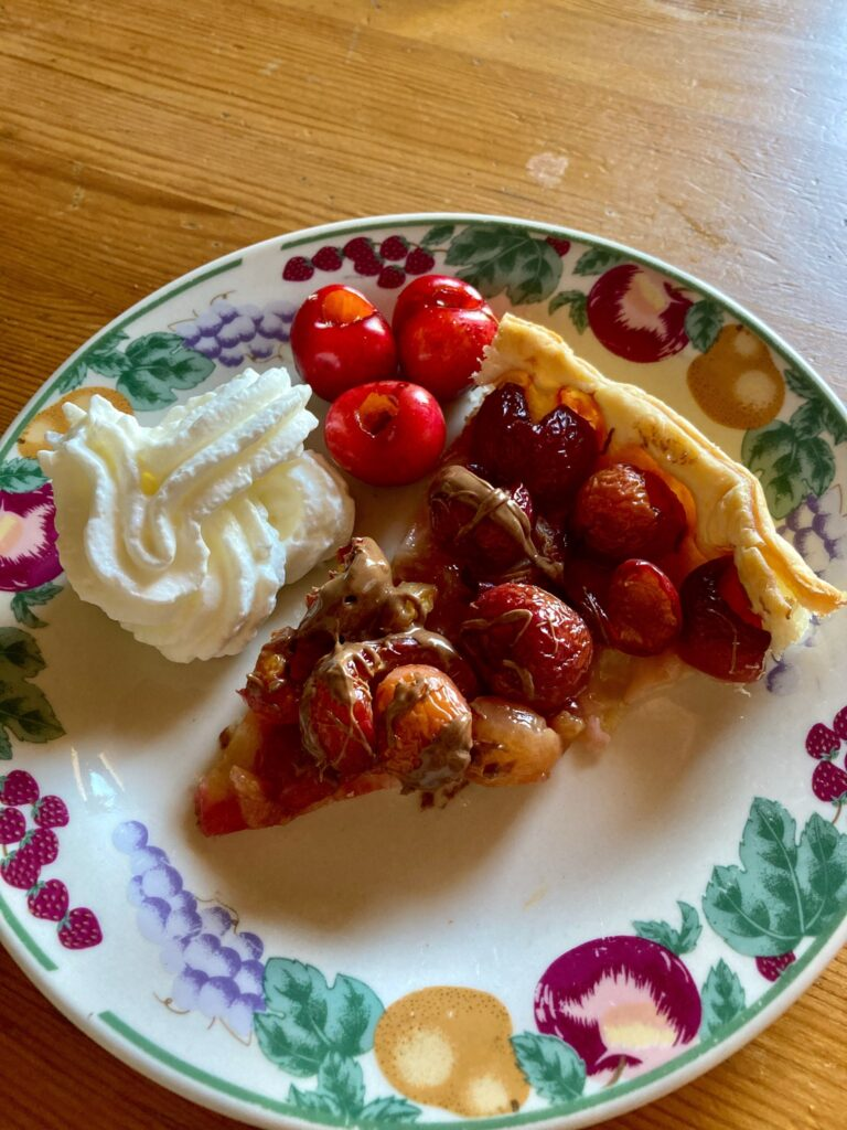 Cherry and chocolate tart slice on a plate with cherries and squirty cream at the side