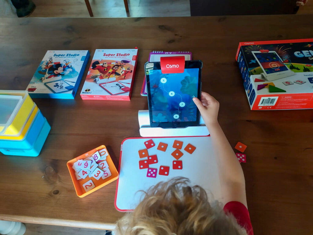 Lucas playing with numbers app, the iPad shows an undersea game and lucas is using dot numbers on his mat
