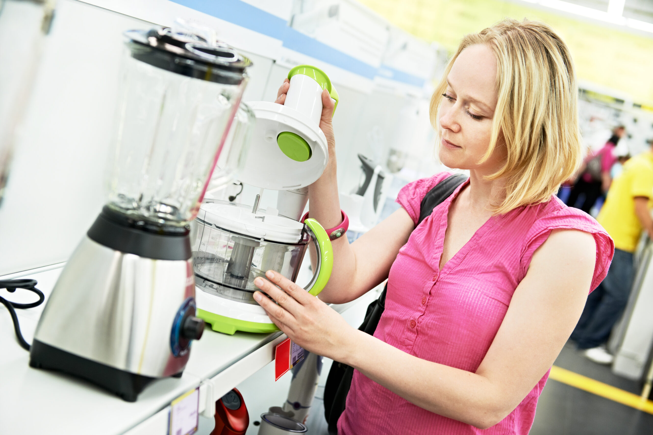 Young woman choosing kitchen processor in home appliance shopping mall supermarket