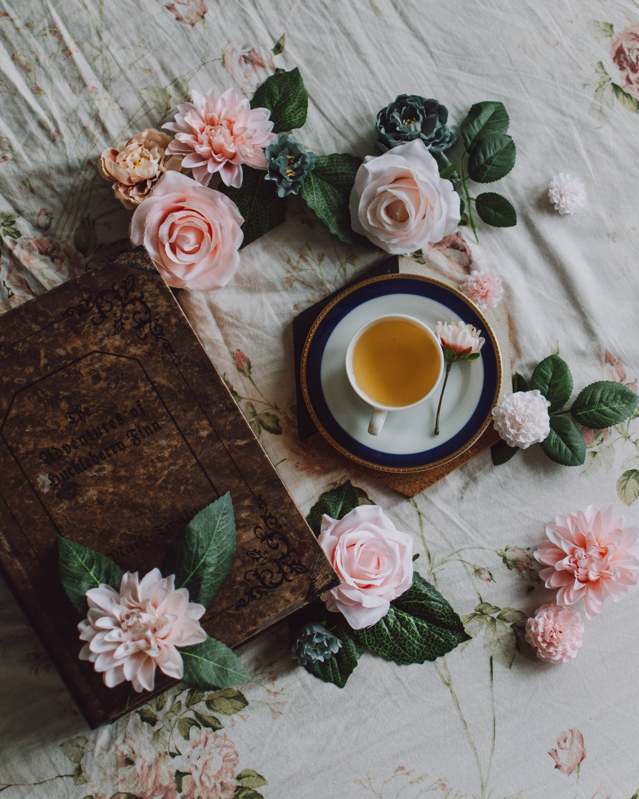 A photo taken from above. You can see a cup of white tea next to a brown book and pink flowers