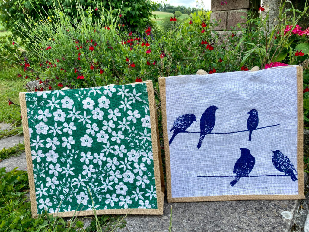 Canvas shopper bags one is white with blue birds. The other is green with white flowers
