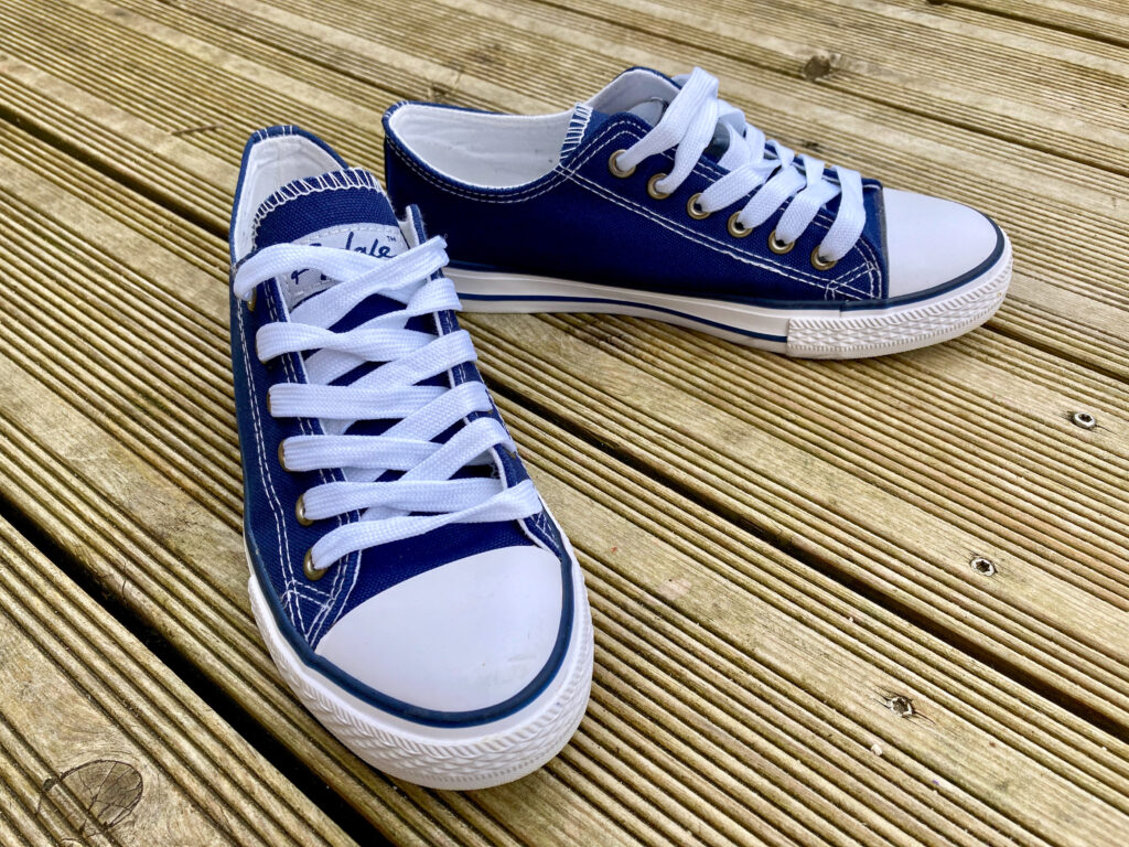 Navy and white canvas trainers on wooden decking