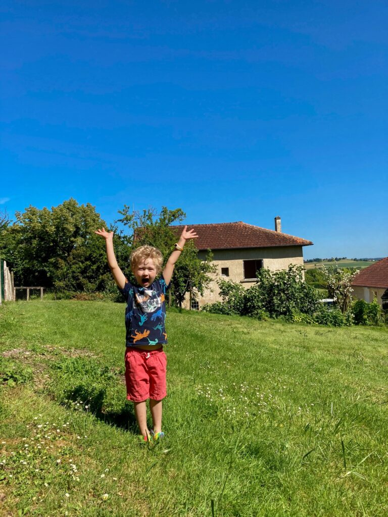 Lucas stood in the garden with his arms up and smiling. The house is in the background