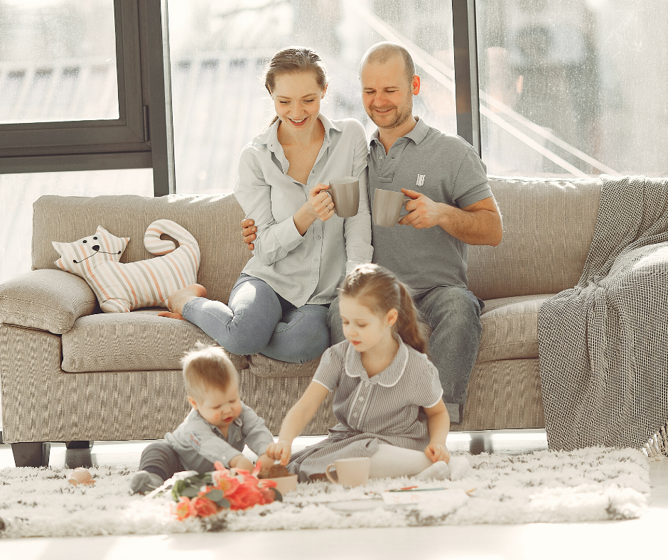 a family sat in the living room. the man and woman are sat on the sofa while a boy an dgirl play with toys on the floor