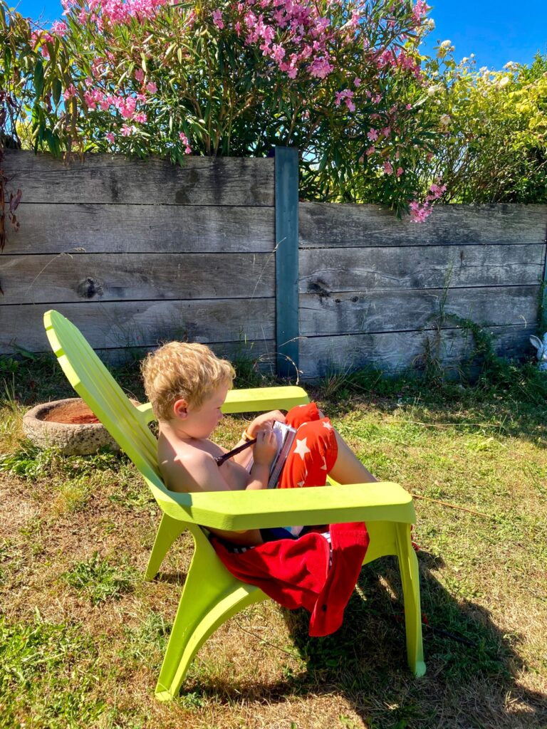 Lucas sat in the garden on a chair writing in his note book