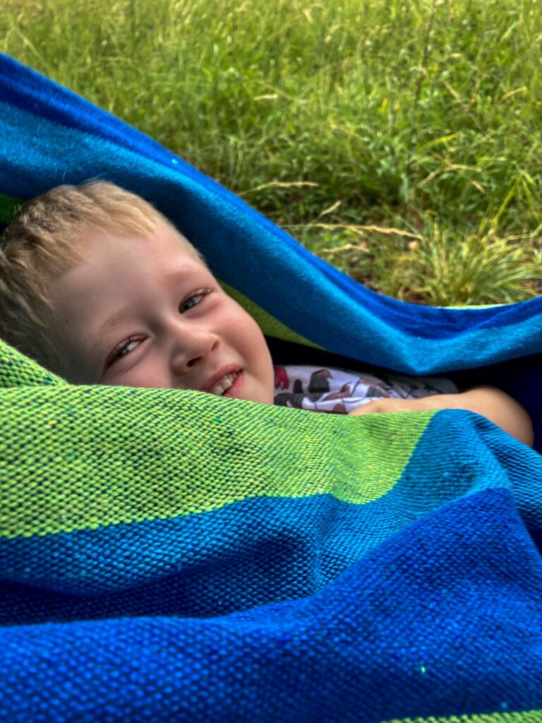 Close up of lucas smiling with green and blue material wrapped round him which is the hammock