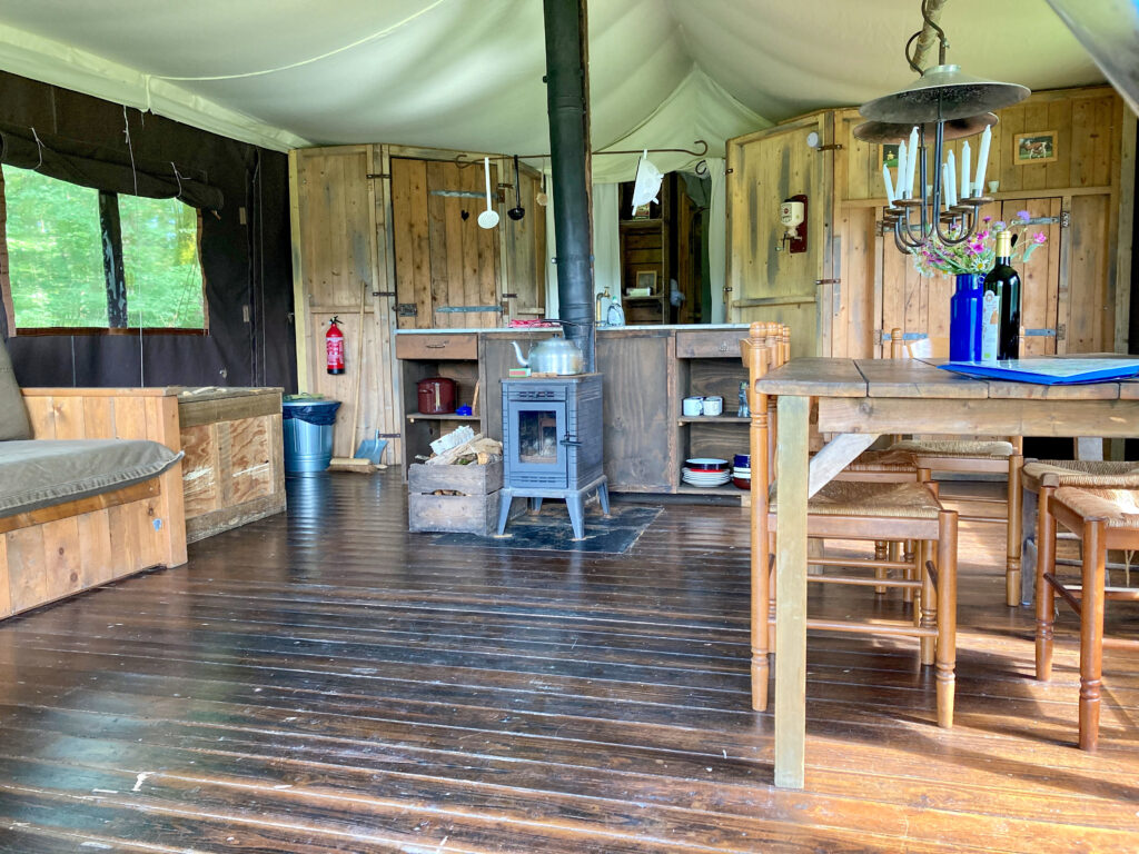 The inside of the glamping tent showing wooden flooring, worktops and a wood fired stove