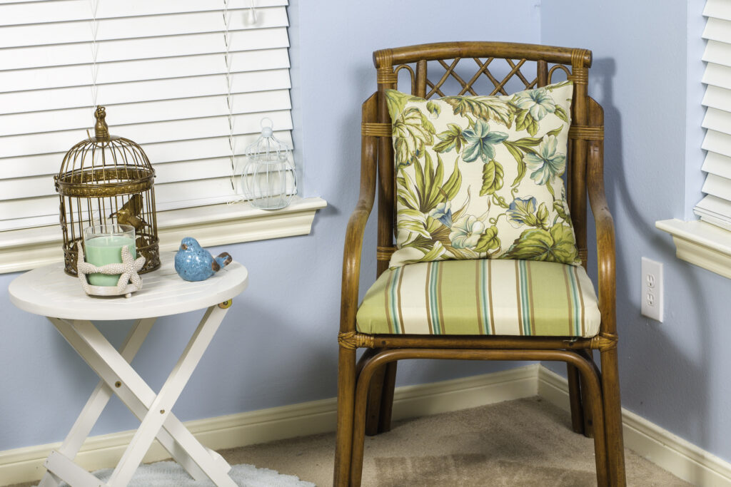A coastal themed indoor shot of a wicker chair.