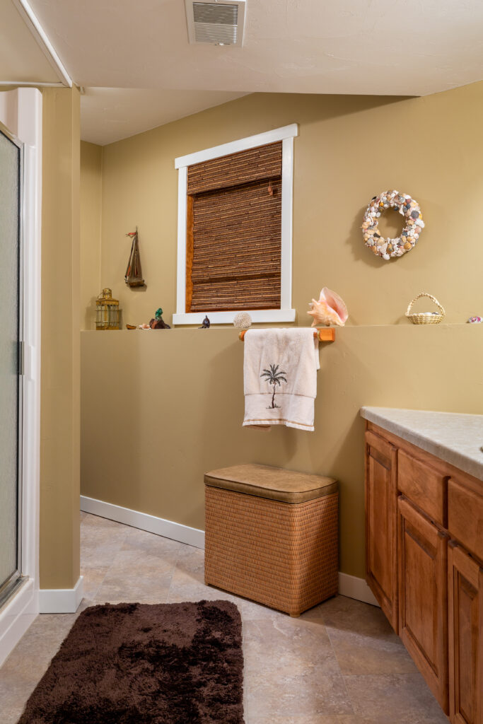 Beach themed guest bathroom that has been remodeled with luxury vinyl tile flooring.