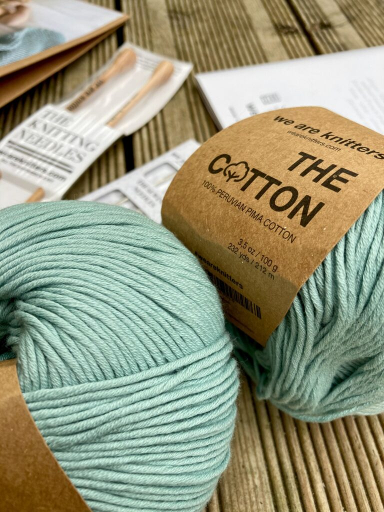 A close up of 2 balls of green cotton yarn