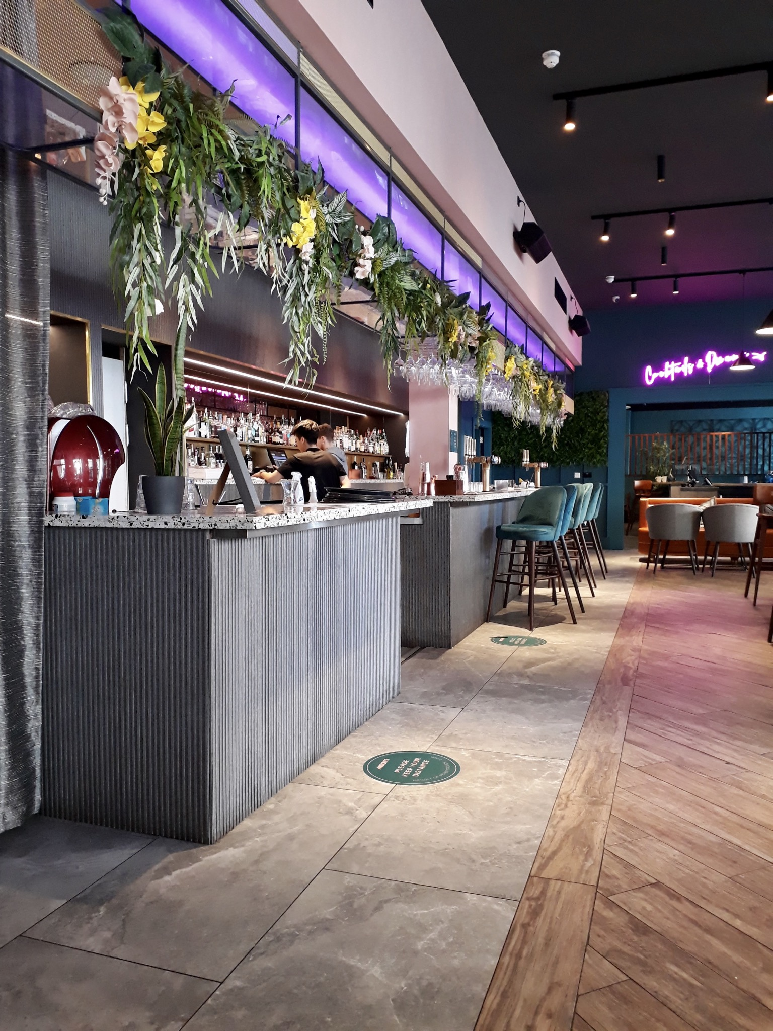 The inside of Mason's Liverpool restaurants you can see a grey bar area with flowers hanging above