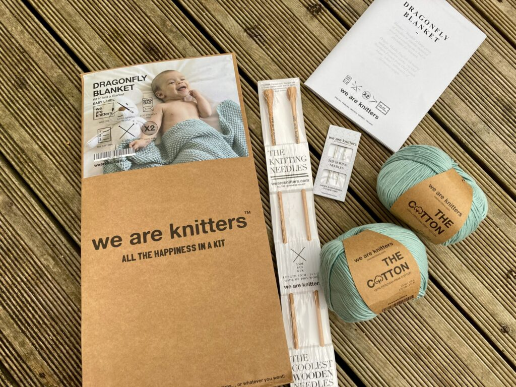 A flatlay of the knitting kit bag with wooden knitting needles, silver sewing needles, instruction booklet and green cotton yarn