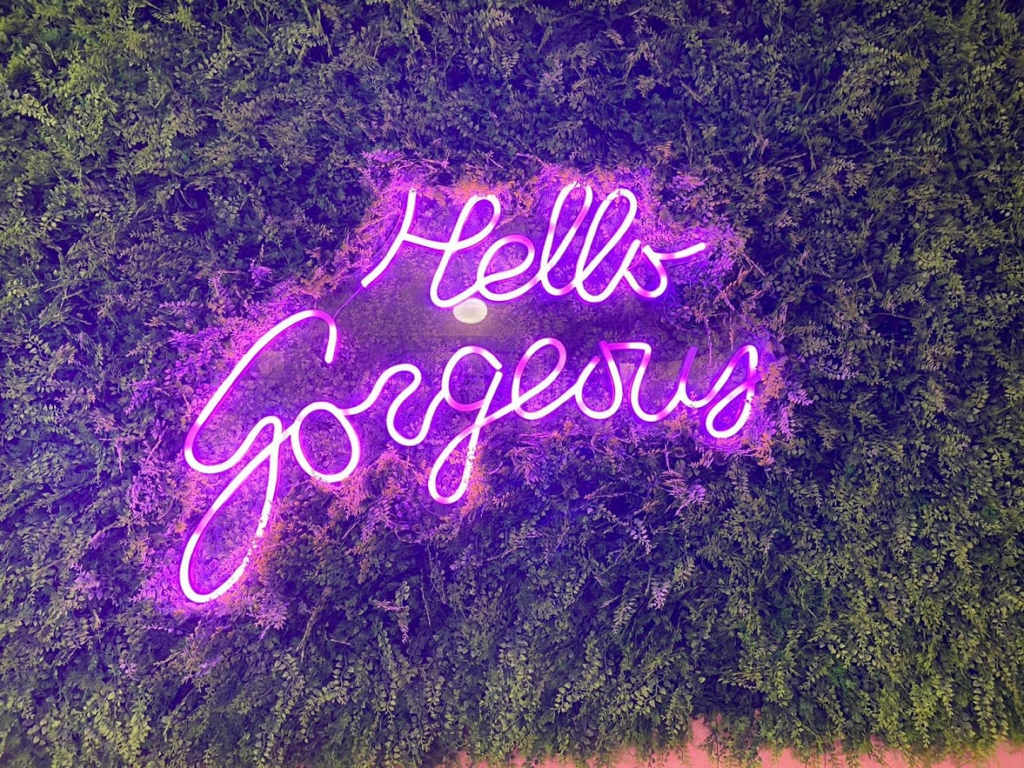 Hello gorgeous pink neon light up sign against greenery