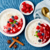 Rice pudding. French milk rice dessert with raspberries, blueberries, berries, jam. Healthy Vegan diet breakfast with coconut milk, cinnamon. Blue linen textile. Top view
