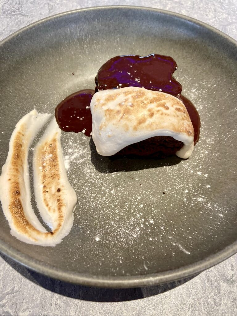 Panne cotta served on a round black plate