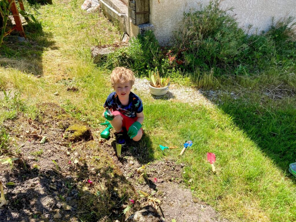 Lucas is kneeling in the garden with his gardening gloves on and childs gardening tools next to him