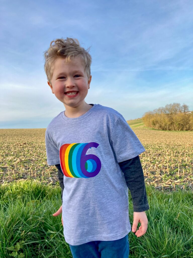 Lucas smiling wearing a multicoloured 6 tshirt
