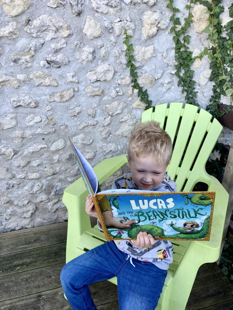 Lucas sat reading Lucas and the Beanstalk book