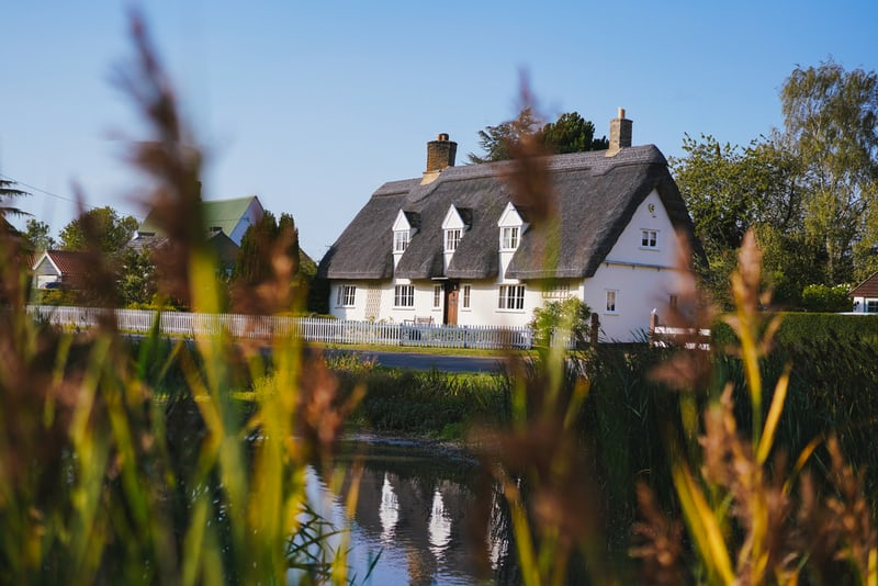 a white cottage with a thatched roof on the river side
