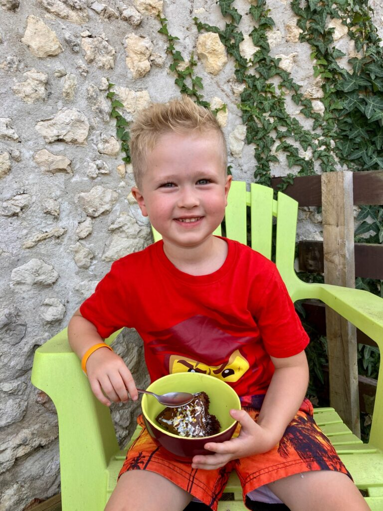 Lucas sat outside smiling at the camera. I'm his hands is a bowl with chocolate and hazelnut cake in with cream drizzled over