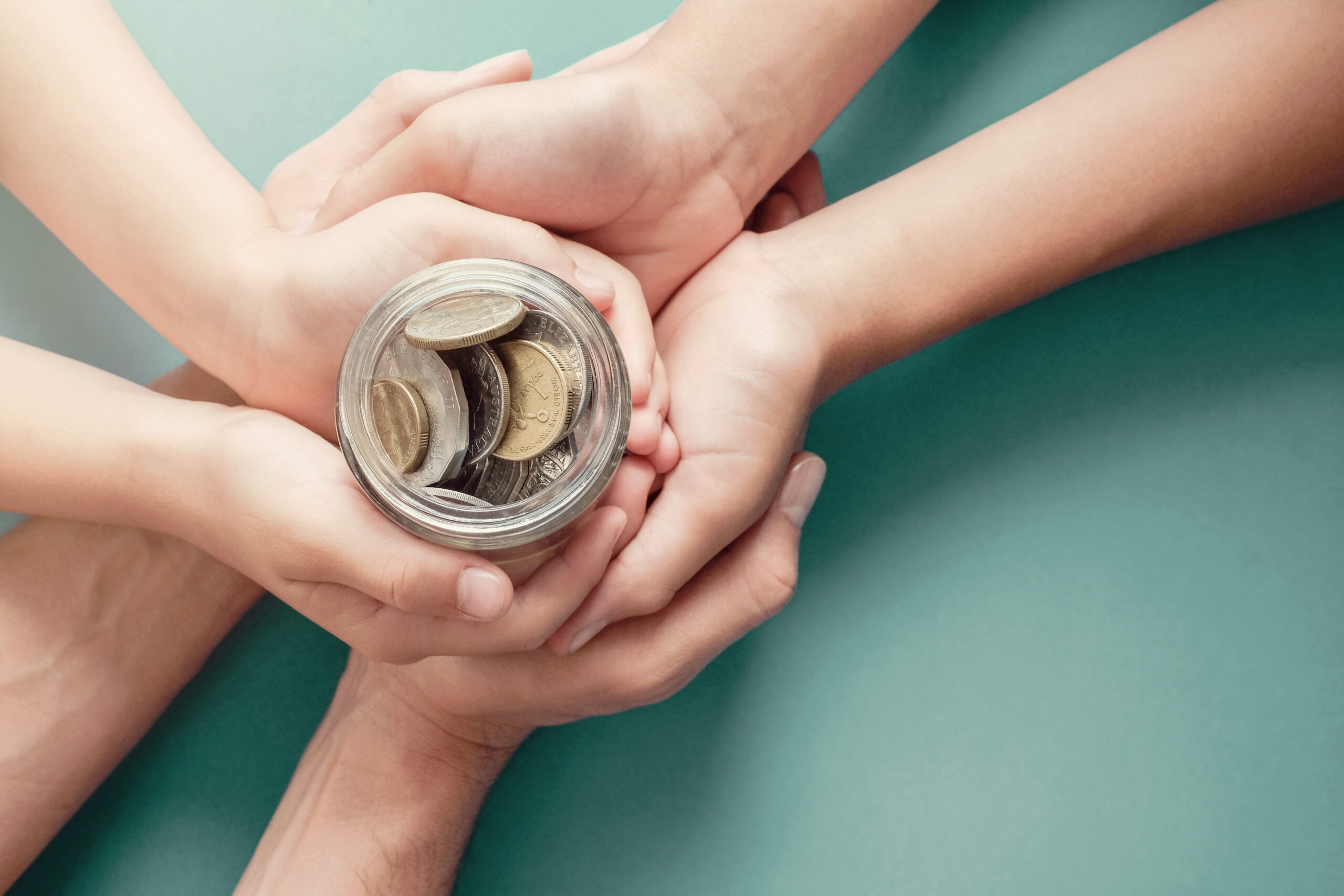 2 pairs of adult hands and a childs hands holding a jar of coins