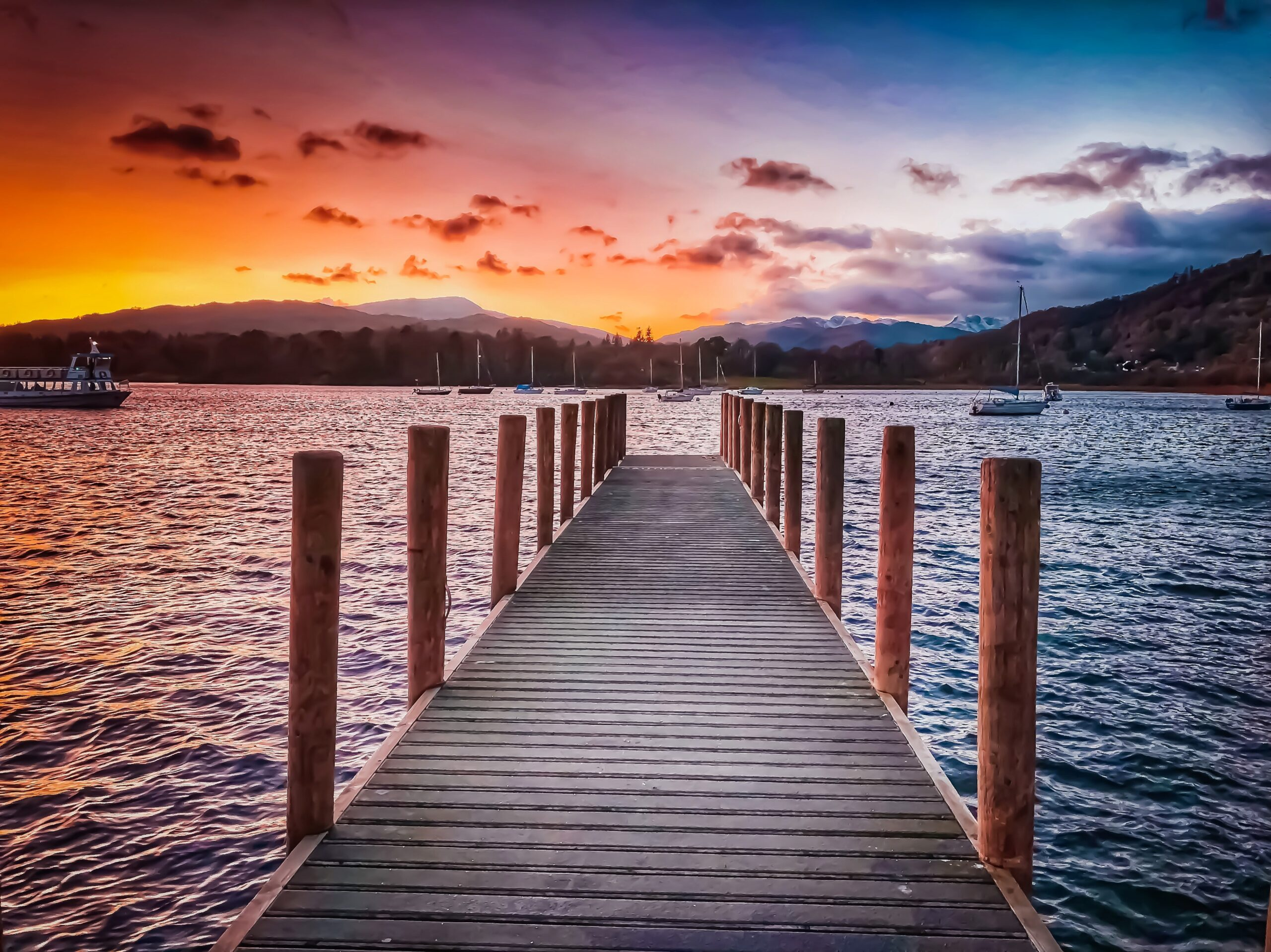 a pier on lake windermere with a sunset in the horizon