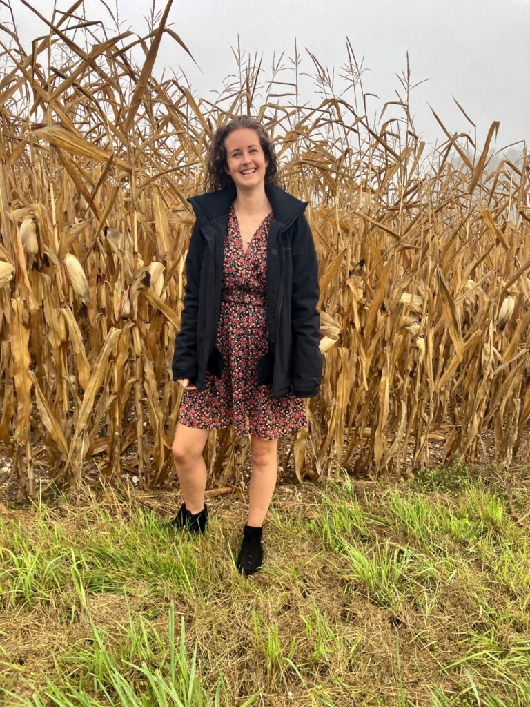 I'm stood next to a corn field wearing a red and black floral dress, black ankle boots and a black coat from protest sportswear