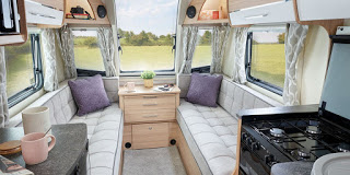 A view of the inside of a bailey caravan showing sofas and a side table