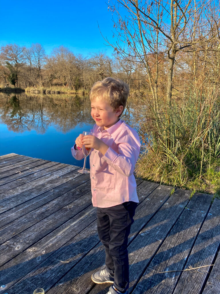 Lucas is stood on decking with a lake behind him. He's wearing a pink shirt and navy trousers. He holding a glass and smiling