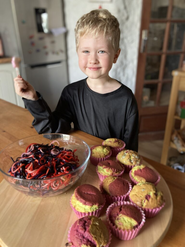 Lucas in the kitchen holding a lolly with cupcakes and red and black spaghetti in front of him