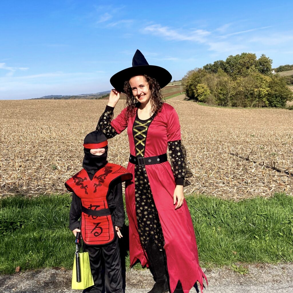Lucas and I stood outside wearing our Halloween costumes. Lucas is a black and red ninja. I'm a black and red witch
