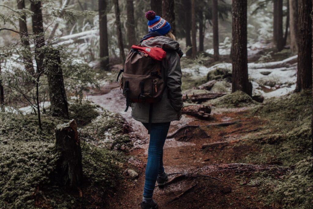 a lady hiking in winter, you can see snow lightly covering the ground. she is wearing a back pack, coat and bob hat