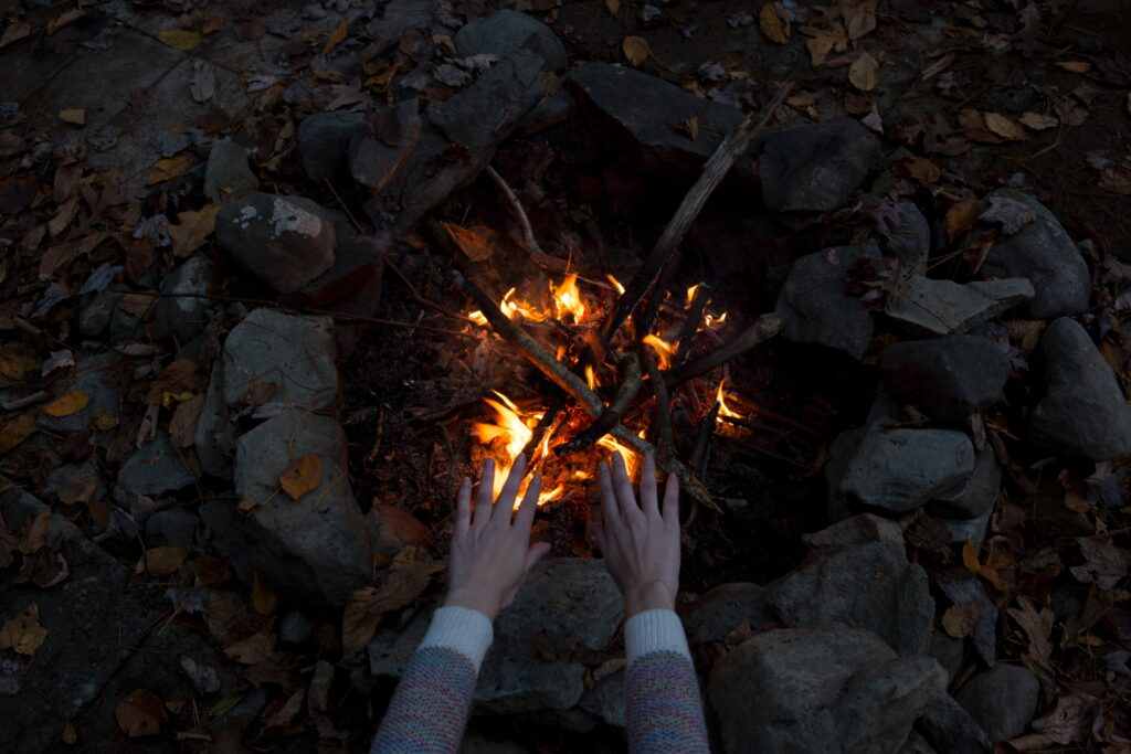 a bonfire showing someone warming their hands on it