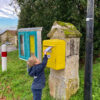 Lucas posting his letter to Pere Noel in a yellow post box