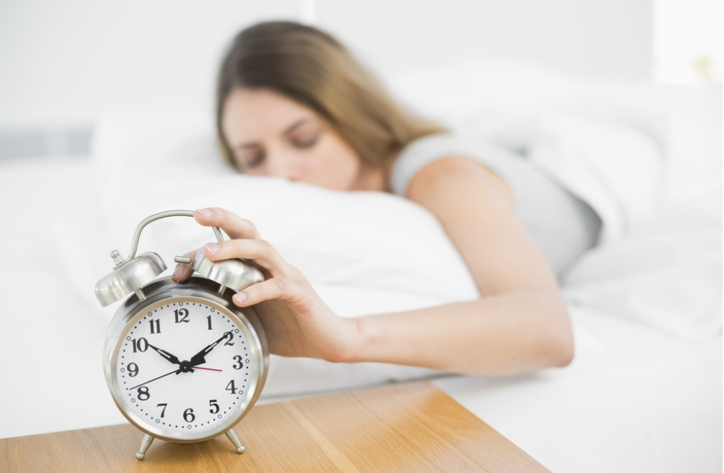 Lady in bed reaching for the alarm clock