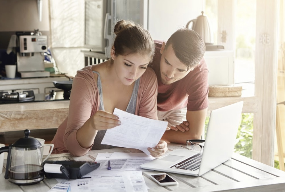 A man and woman looking over paperwork and a laptop