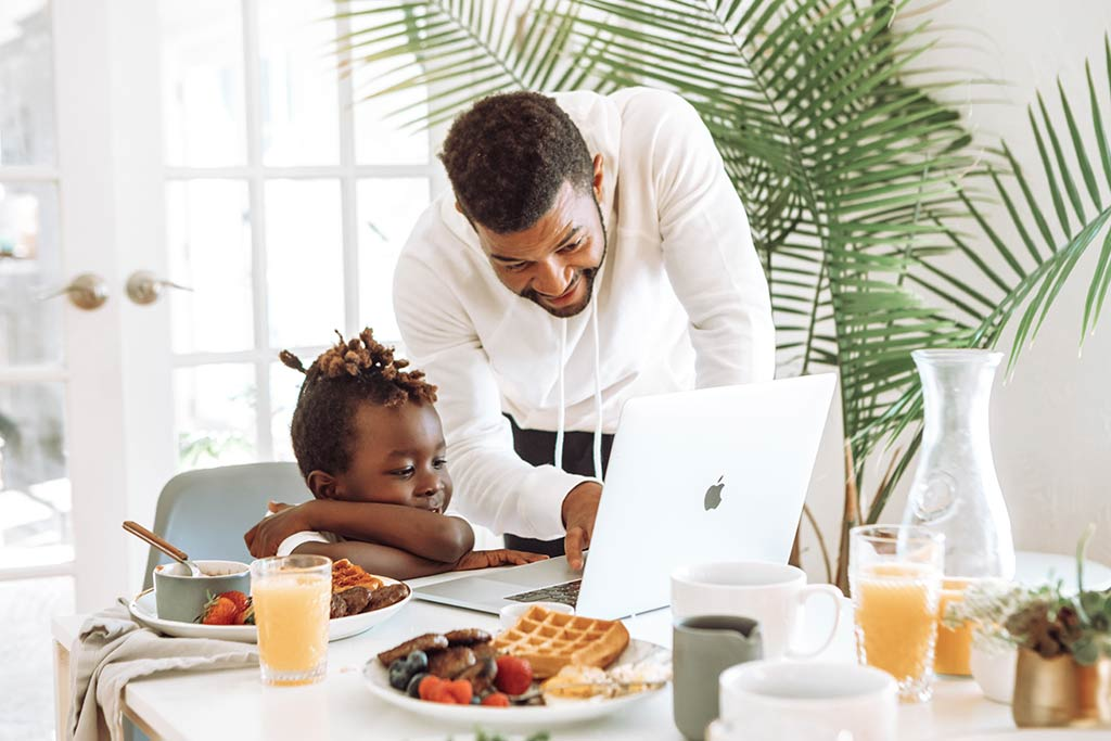 man at the dining table with chold pointing at the laptop with breakfast things on the table