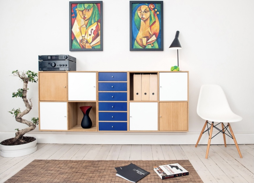 A set of drawers against a wall with wall art on