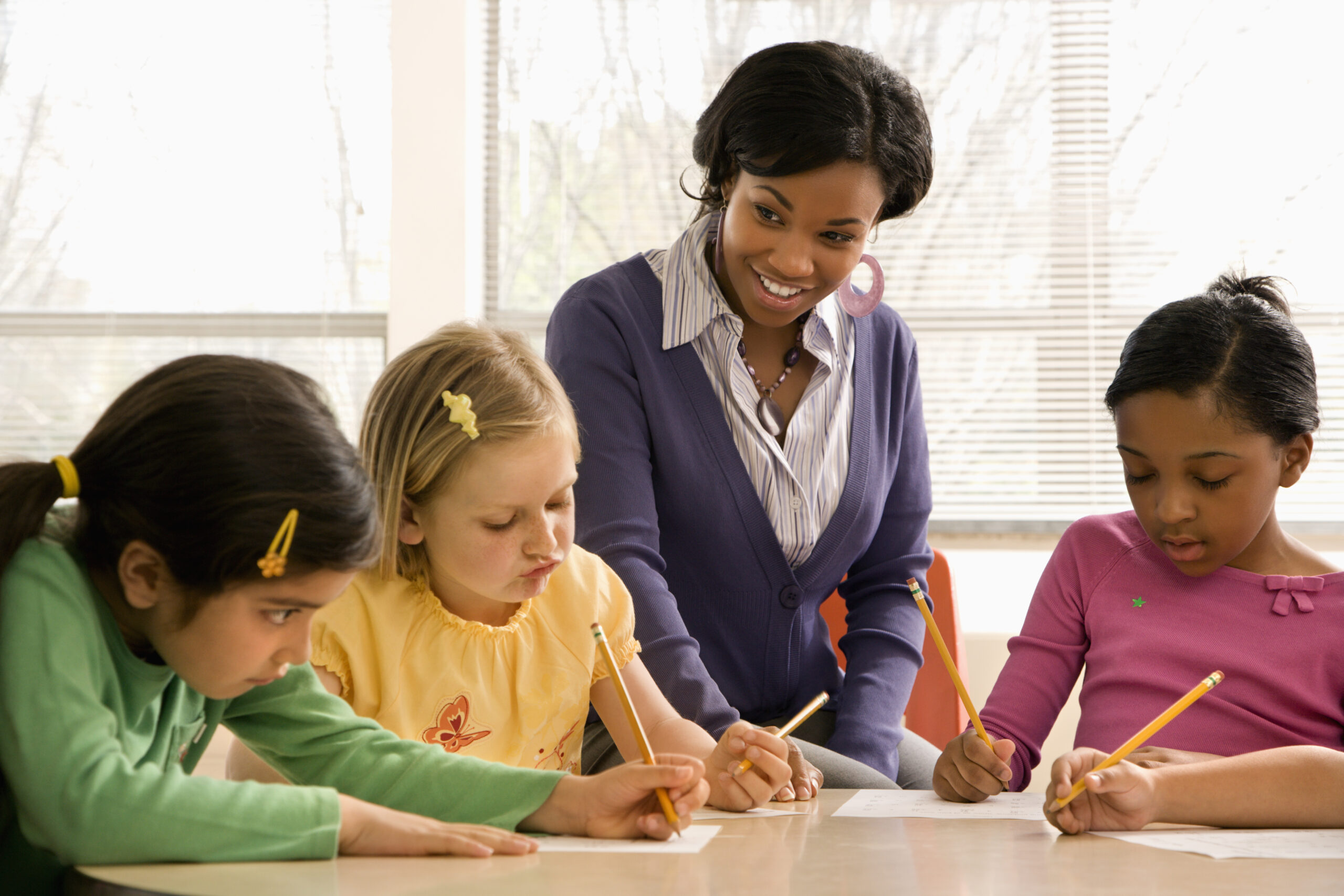three children wiritng at a desk with an adult sat smiling at them. Teacher helping students in school classroom. Horizontally framed shot.