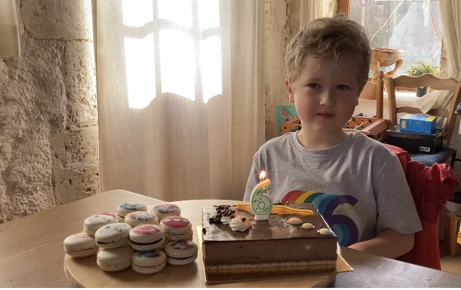 Lucas with a choc cake and macaroons